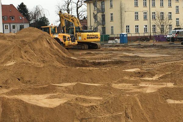 Der Bagger schaufelt kräftig und verteilt den Sand